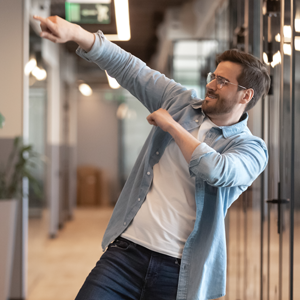 man in office hallway doing a celebratory dance