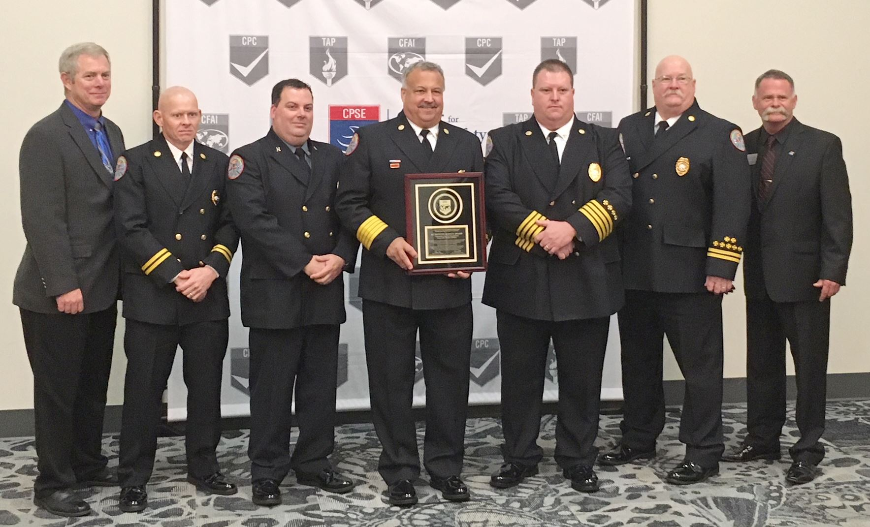 GCFD Chief Kovalcik and firefighters holding their international accrediation plaque